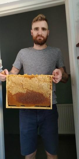 Damian Śmiarowski prezentujący plaster miodu.