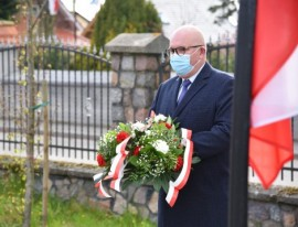 Wiceburmistrz Piotr Wittbrodt podczas składania kwiatów na zbiorowej mogile